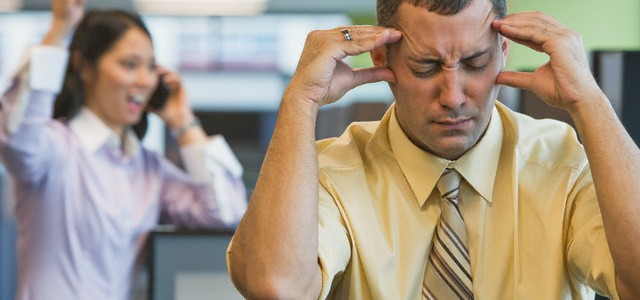 man in office bothered by loud coworkers