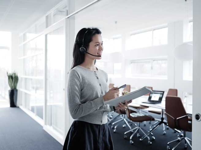 business woman in office wearing wireless headset