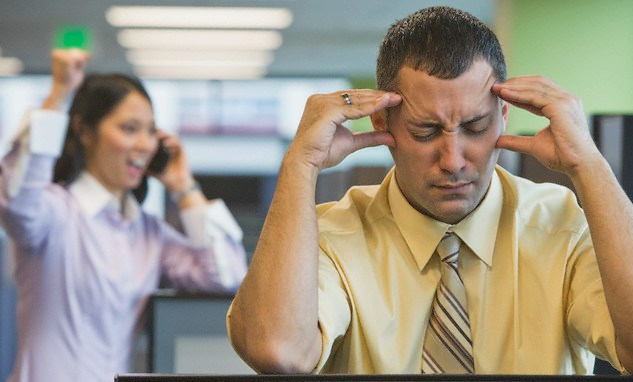 businessman in foreground bothered by sound and co-worker in background loudly talking on phone